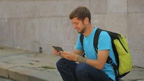Viaggiatore con zaino e sacco a pelo maschio che si siede sul bordo della strada, esaminante il suo smartphone, itinerario turist archivi video