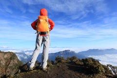 viaggiatore con zaino e sacco a pelo risoluto della donna che fa un'escursione sul picco di montagna Immagine Stock