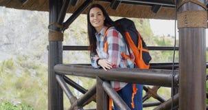Viaggiatore con zaino e sacco a pelo sorridente su un'allerta della montagna Immagine Stock