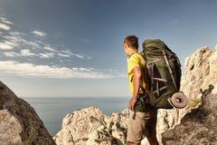 Viaggiatore con zaino e sacco a pelo su alta roccia Fotografia Stock