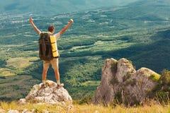 Viaggiatore con zaino e sacco a pelo su alta roccia ed esaminare la valle Fotografie Stock Libere da Diritti
