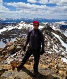 Viaggiatore con zaino e sacco a pelo su una parte superiore della montagna del Colorado Fotografia Stock