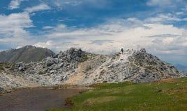 Viaggiatore con zaino e sacco a pelo sul passo di montagna Fotografie Stock