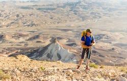 Viaggiatore con zaino e sacco a pelo turistico dell'uomo dell'alpinista che sta guardante il deserto di vista Fotografia Stock Libera da Diritti