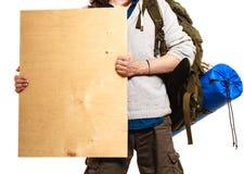 Viaggiatore con zaino e sacco a pelo umano con l'annuncio di legno in bianco dello spazio della copia Immagine Stock Libera da Diritti