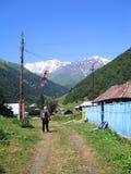 Viaggiatore con zaino e sacco a pelo in villaggio montagnoso caucasico Fotografia Stock Libera da Diritti