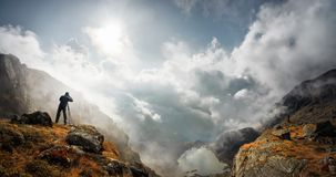 Viaggiatore del fotografo con la macchina fotografica che prende foto delle montagne stan Immagini Stock