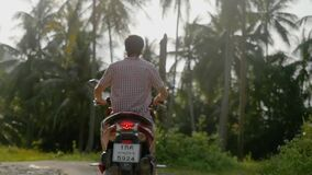 Viaggiatore del giovane che conduce motocicletta sulla strada soleggiata tropicale in una giungla Movimento lento 1920x1080 stock footage