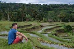 Viaggiatore del giovane che si siede e che si rilassa all'aperto alle risaie su a terrazze in Bali Indonesia Fotografie Stock