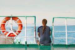 Viaggiatore del giovane che si siede sulla barca e che esamina acqua Fotografie Stock