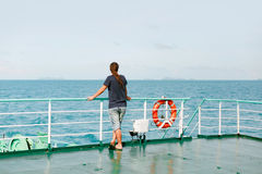 Viaggiatore del giovane che sta sulla barca e che esamina acqua Fotografia Stock Libera da Diritti