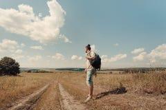 Viaggiatore del giovane sulla strada alla campagna Fotografie Stock
