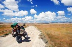 Viaggiatore del motociclo di enduro con le valigie che stanno su una strada non asfaltata Immagini Stock