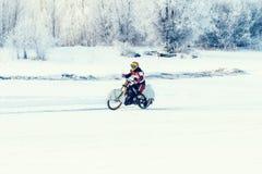 Viaggiatore del motociclo sul percorso della strada della steppa di inverno della neve Immagine Stock