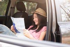 Viaggiatore dell'automobile della giovane donna con la mappa immagine stock libera da diritti