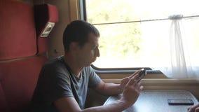 Viaggiatore dell'uomo che si rilassa sul treno che ascolta la musica e che sorride attraverso le immagini via i media sociali vid archivi video