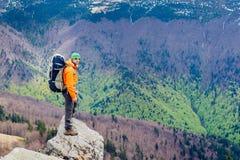 Viaggiatore dell'uomo che sta su una cima della montagna Priorità bassa della foresta Immagini Stock