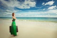 Viaggiatore della donna alla spiaggia con la valigia che parla sul telefono cellulare Fotografie Stock Libere da Diritti