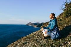 viaggiatore della donna che si siede sopra una scogliera e che esamina mare fotografie stock