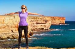 Viaggiatore della donna che sta le mani all'aperto sollevate al cielo blu Immagine Stock Libera da Diritti