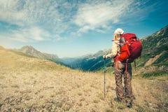 Viaggiatore della donna con alpinismo rosso dello zaino Immagini Stock