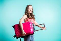 Viaggiatore della donna con la valigia sul fondo di colore La bella ragazza castana in cima e jeans rosa sta su fondo blu fotografie stock
