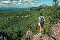 Viaggiatore della donna con lo zaino che fa un'escursione in montagne con bello paesaggio Fotografia Stock Libera da Diritti