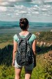 Viaggiatore della donna con lo zaino che fa un'escursione in montagne con bello paesaggio Fotografia Stock