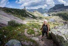 Viaggiatore della donna con lo zaino che fa un'escursione in montagne con il bello paesaggio dell'Himalaya sullo sport di alpinis Fotografia Stock