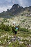 Viaggiatore della donna con lo zaino che fa un'escursione in montagne con il bello paesaggio dell'Himalaya sullo sport di alpinis Immagine Stock