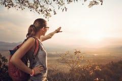 Viaggiatore della donna dei pantaloni a vita bassa con lo zaino che gode della vista del tramonto fotografie stock