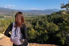 Viaggiatore della donna dell'Asia che guarda fuori per osservare sulla montagna di punta fotografia stock
