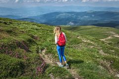 Viaggiatore della donna, ragazza con l'esterno di camminata di estate delle montagne dello zaino immagini stock