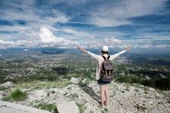 Viaggiatore della donna sull'alta montagna, mani su nell'aria Immagini Stock
