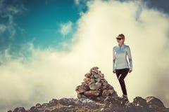 Viaggiatore della donna sulla sommità della montagna con le pietre Immagine Stock