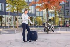 Viaggiatore della giovane donna che manda un sms su un telefono cellulare Fotografia Stock