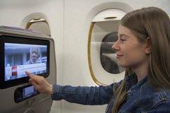 Viaggiatore della giovane donna che per mezzo del touch screen a bordo Fotografia Stock