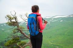 Viaggiatore della giovane donna con lo zaino che fa un'escursione in montagne con il damerino Fotografia Stock Libera da Diritti