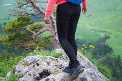Viaggiatore della giovane donna con lo zaino che fa un'escursione in montagne con il damerino Immagini Stock
