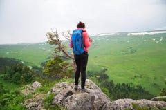 Viaggiatore della giovane donna con lo zaino che fa un'escursione in montagne con il damerino Fotografia Stock
