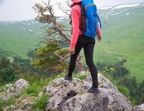Viaggiatore della giovane donna con lo zaino che fa un'escursione in montagne con il damerino Fotografie Stock Libere da Diritti