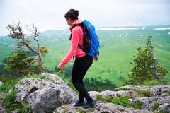 Viaggiatore della giovane donna con lo zaino che fa un'escursione in montagne con il damerino Immagine Stock Libera da Diritti
