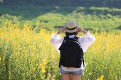 Viaggiatore della giovane donna con lo zaino che gode e che sta sul flusso fotografia stock