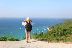Viaggiatore della giovane donna con lo zaino che gode e che sta sulle montagne dei precedenti del mare, Koh Larn nella città di P fotografia stock libera da diritti