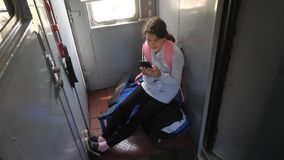 Viaggiatore della ragazza dell'adolescente con uno zaino che si siede sugli zainhi delle borse alla finestra dello stile di vita  video d archivio