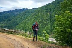 Viaggiatore felice sulla strada della montagna Fotografia Stock Libera da Diritti