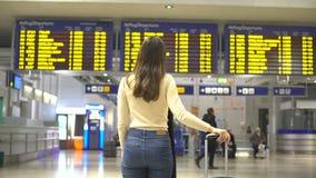 Viaggiatore femminile che esamina informazioni in aeroporto, viaggio di registrazione di partenza stock footage
