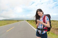 Viaggiatore femminile che sta sul bordo della strada dell'asfalto Fotografia Stock