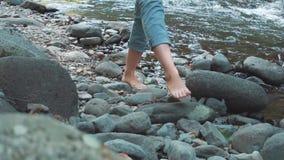 Viaggiatore giovane scalzo di fucilazione alle passeggiate da vicino e turistiche senza scarpe sulle pietre lungo il fiume freddo video d archivio