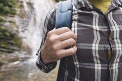 Viaggiatore irriconoscibile dell'uomo con i supporti dello zaino con la sua parte posteriore sul primo piano del fondo della casc fotografia stock libera da diritti